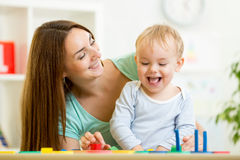 Kind und Mutter, die bei Tisch spielen lizenzfreies stockbild