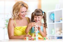 Kind und Mutter, die zu Hause hölzerne Spielwaren spielen Lizenzfreies Stockbild