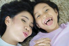 Kind und Mutter, die zusammen auf dem Teppich liegen Stockbild