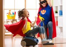 Kind und Mutter gekleidet als Superhelden, die Staubsauger im Raum verwenden Frau und Tochter der Familie von mittlerem Alter hab Stockfotografie