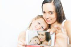 Kind und Mutter machen selfie am Handy, gute Kamera Stockfotografie