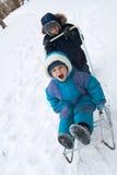 Kind und Schätzchen auf Schlitten Lizenzfreies Stockfoto