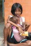 Kind und Schätzchen sitzen das Bitten um Geld in Kambodscha. lizenzfreies stockfoto