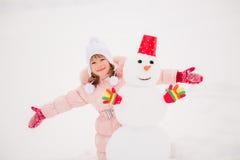 Kind und Schneemann im Winter lizenzfreies stockfoto