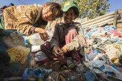 Kind und seine Eltern während des Mittagessens im Bruch zwischen dem Arbeiten an Dump Lizenzfreie Stockfotos