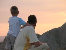 Kind und Vater, die auf Sonnenuntergang schauen Stockbilder