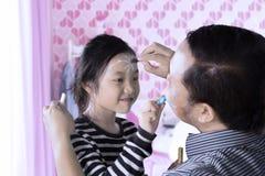 Kind und Vater, die Gesichtsmalerei tun Stockfotos