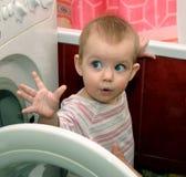 Kind und Waschmaschine Stockfotos