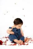 Kind unter Blumen-Blumenblättern Stockfoto