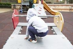 Kind unter zwei Jahren, die im Park mit einer grauen Jacke und blauen Hosen spielen lizenzfreies stockbild