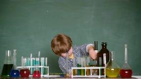 Kind van basisschool Schooljongen De kleine verdienende chemie van de jonge geitjeswetenschapper in schoollaboratorium Biologieex stock video