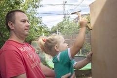 Kind, Vater und ein Hammer Stockfotos