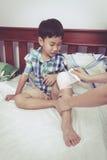 Kind verletzt Mutter, die das Knie des Sohns verbindet Abbildung der roten Lilie Stockbild