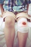 Kind verletzt Wunde auf dem Knie des Kindes mit Verband Weinlese s Stockbild