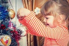 Kind verzieren den Weihnachtsbaum stockfotografie