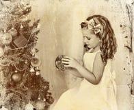 Kind verzieren Weihnachtsbaum Altes Foto auf gelbem Papier Stockfotos