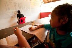 Kind von den armen Bereichen im lession an der Schule Stockbilder
