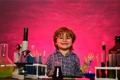 Kind von der Volksschule Junior-Jahr-Chemie Biologieexperimente mit Mikroskop Ausbildung Chemielektion A lizenzfreies stockfoto