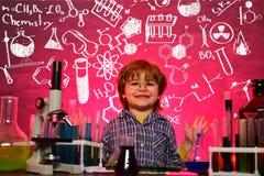 Kind von der Volksschule Junior-Jahr-Chemie Biologieexperimente mit Mikroskop Ausbildung Chemielektion A stockbild