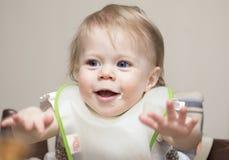 Kind von einjährigem füttern mit dem Löffel Stockfoto