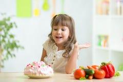 Kind wählend zwischen gesundem Gemüse und geschmackvoll stockbilder