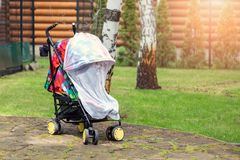 Kind in wandelwagen omvat met beschermende netto tijdens gang Kinderwagen met anti-mug witte dekking mug stock fotografie