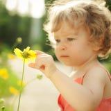 Kind wat betreft de lentebloem Stock Foto