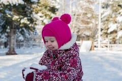 Kind am Weihnachten mit Schnee in den Palmen Stockfotografie