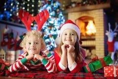Kind am Weihnachtsbaum Kinder am Kamin auf Weihnachten stockbild