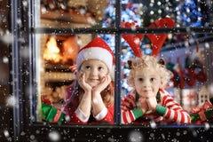 Kind am Weihnachtsbaum Kinder am Kamin auf Weihnachten lizenzfreies stockfoto