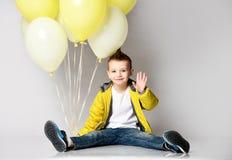 Kind, welches das B?ndel von den Ballonen bleiben auf dem Knie ?ber dem wei?en Hintergrund h?lt lizenzfreie stockfotografie