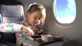 Kind, welches das gesunde Mittagessen im Flugzeug isst stock video footage