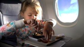 Kind, welches das gesunde Mittagessen im Flugzeug isst stock video