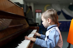 Kind, welches das Klavier spielt Stockbild