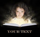 Kind, welches das magische Buch liest Stockbild