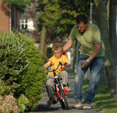 Kind, welches das Radfahren erlernt Stockfotos