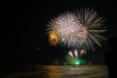 Kind, welches die Feuerwerke sich reflektieren im Wasser in Stärke dei Mrz schaut Stockfotografie
