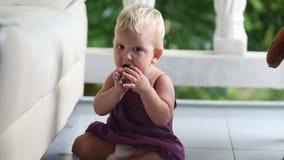 Kind, welches die Gurke steht isst, lehnend auf dem Sofa stock footage
