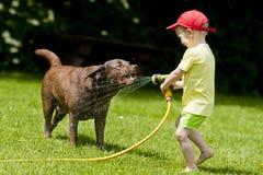 Kind, welches die Hundewasserkühlung spielt Lizenzfreie Stockbilder
