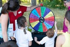 Kind, welches die Radlotterie im Park spinnt lizenzfreies stockbild