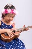 Kind, welches die Ukulele/Kind spielen Ukulele-Hintergrund spielt Stockbild