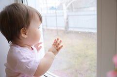 Kind, welches heraus das Fenster herbeisehnt etwas Sonnenschein wegen des Regens schaut Neugier childness Lizenzfreie Stockbilder