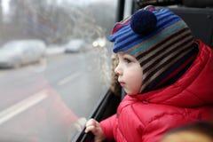Kind, welches heraus das Fenster schaut Stockfotografie