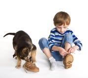 Kind, Welpe und Schuhe Stockfotos
