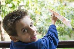 Kind wirft Papierfläche Stockbild
