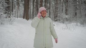 Kind woman, dressed in a bright pink hat and gloves, long white jacket with hood, black pants, fun talking friend on stock video