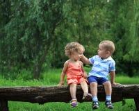 Kind words. Children sitting on bench in summer park stock images