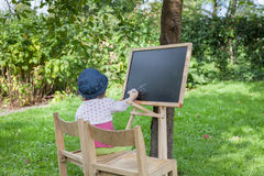 Kind zeichnet auf das Brett Stockbilder