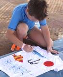 Kind zeichnet auf ein weißes T-Shirt Lizenzfreie Stockfotografie