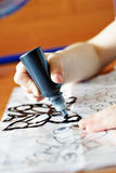 Kind zeichnet beflecktes Schwarzes. Schätzchenabbildungen auf Glas. Stockfoto